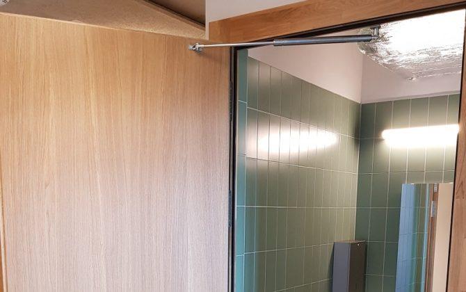 Türöffnungsbegrenzer an der Toilettentür in einer Schule